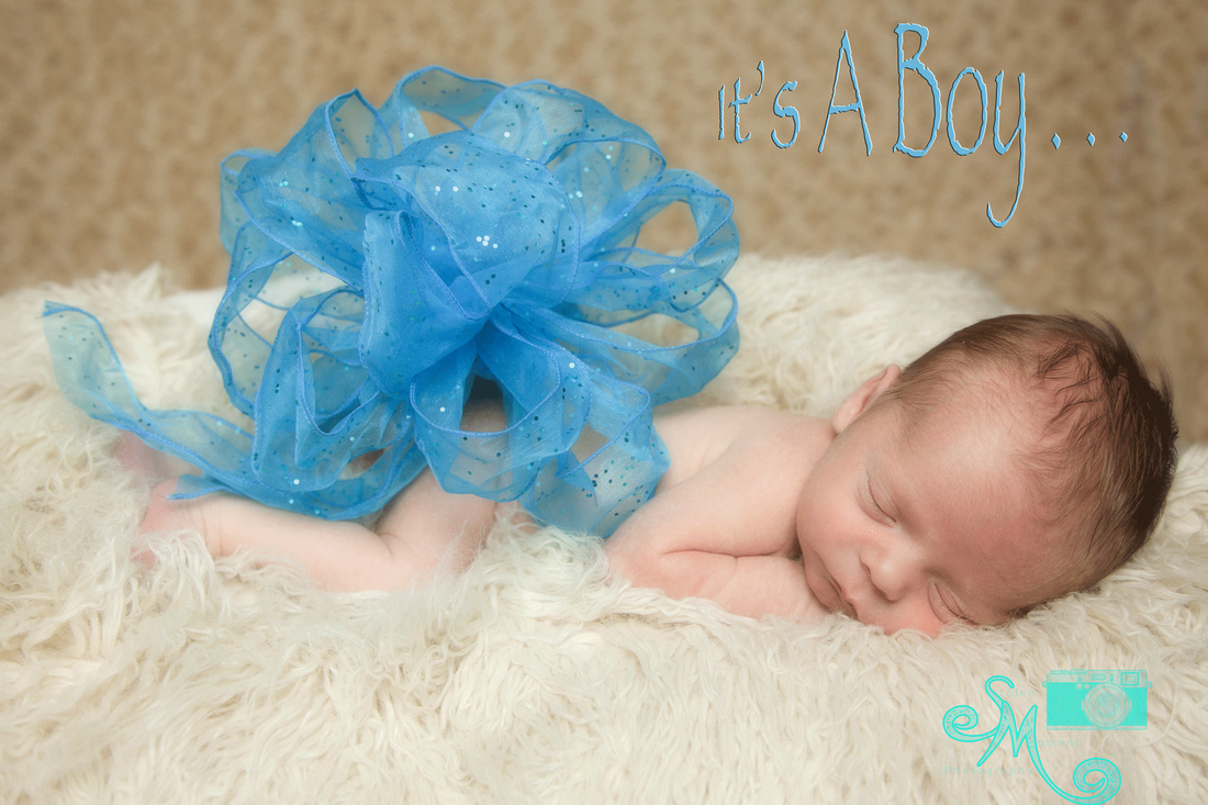 a newborn boy sleeping with a big blue bow on his back