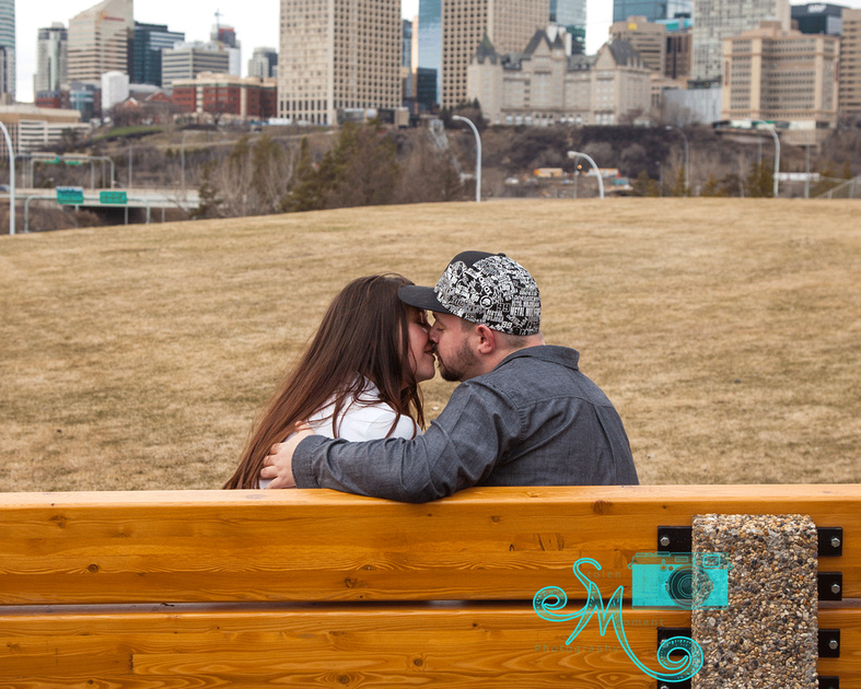 man and his fiancé sitting on bench kissing with city skyline in background