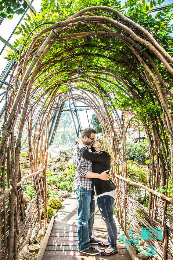 woman and her fiancé kiss under an arbour of branches