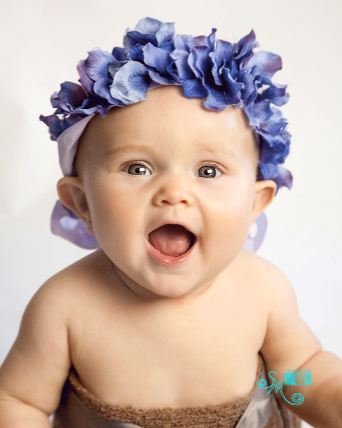 gerber like baby with purple flower crown smiling at camera