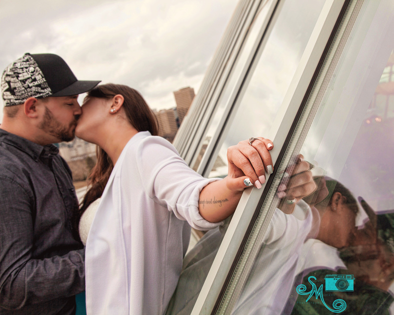 man and his fiancé kiss with a reflection of them in the muttart pyramid