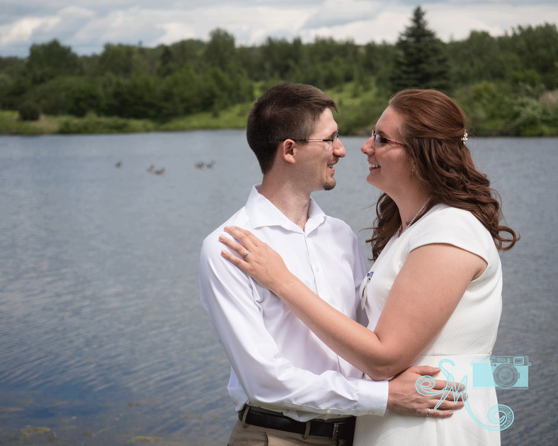 man and woman standing in front of lake looking into each other's eyes
