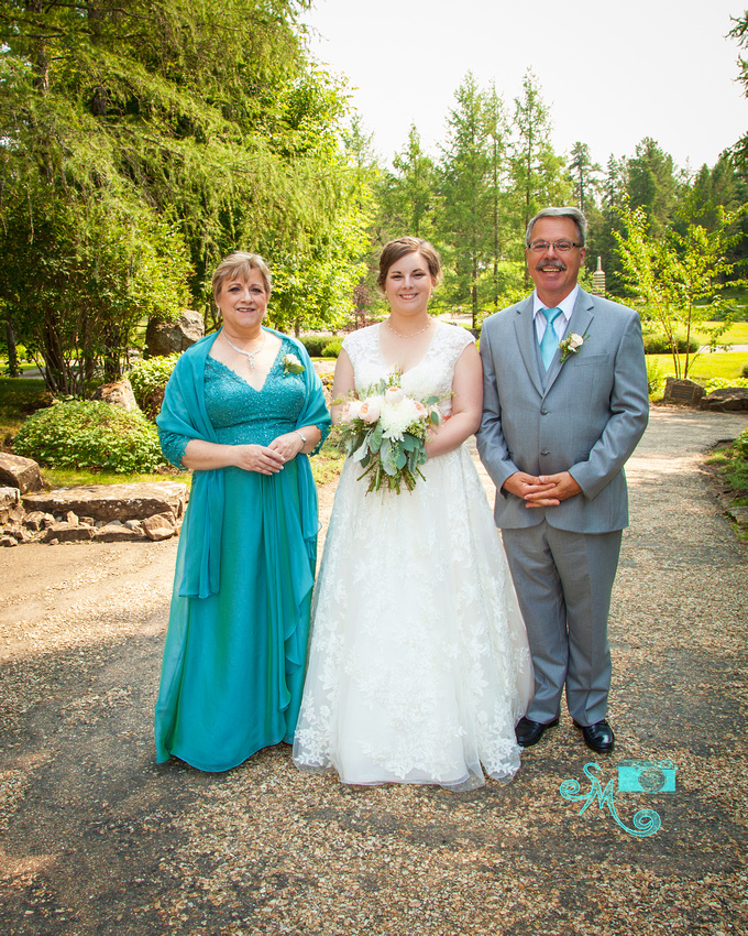 the bride poses with her parents