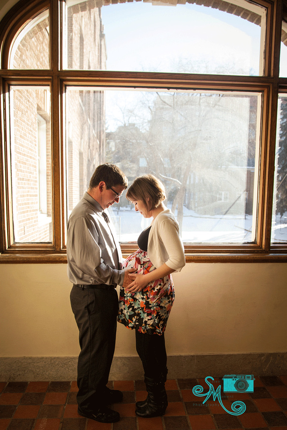 a mom and dad to be hold the belly while standing in front of a large window with the sun pouring in
