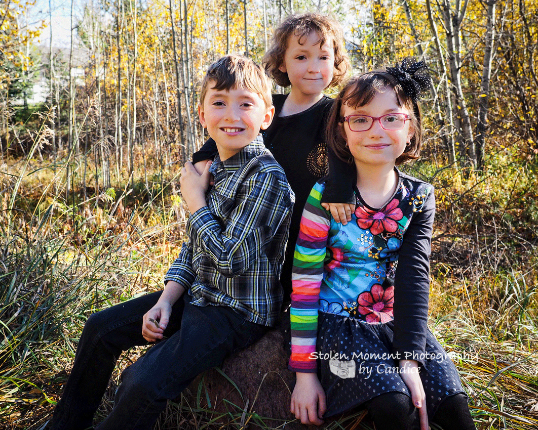 three siblings sitting on a rock