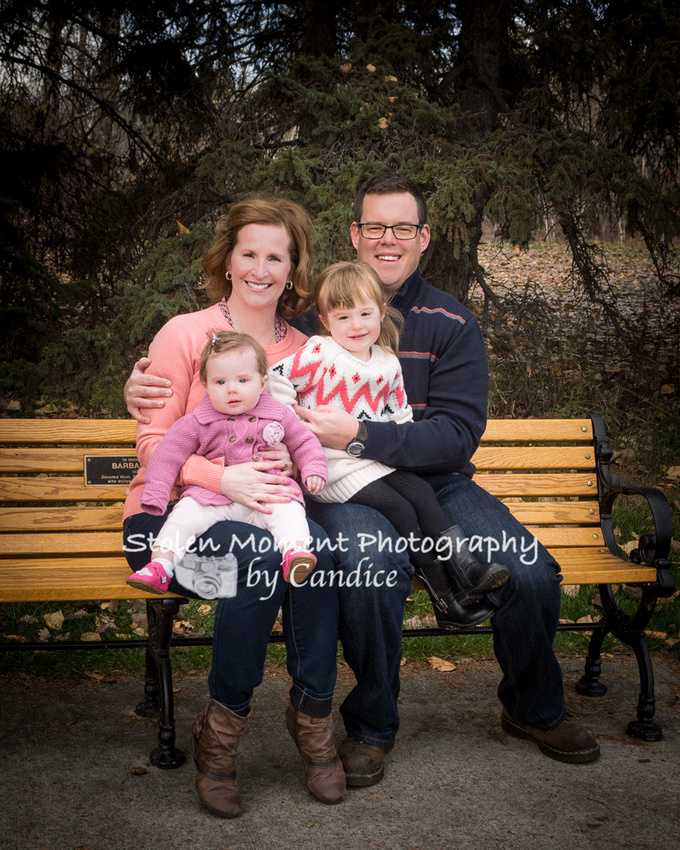 family of four sitting on bench in Hawrelak park