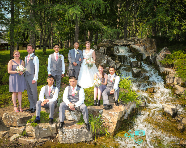 The bride and groom with their wedding party pose by the Japanese garden's waterfall