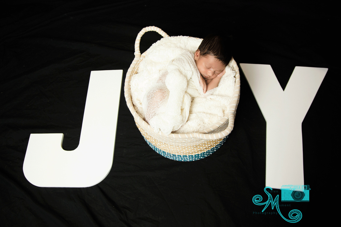 "a baby boy sleeps peacefully in a round basket which forms the letter ""O"" in the word ""Joy"""