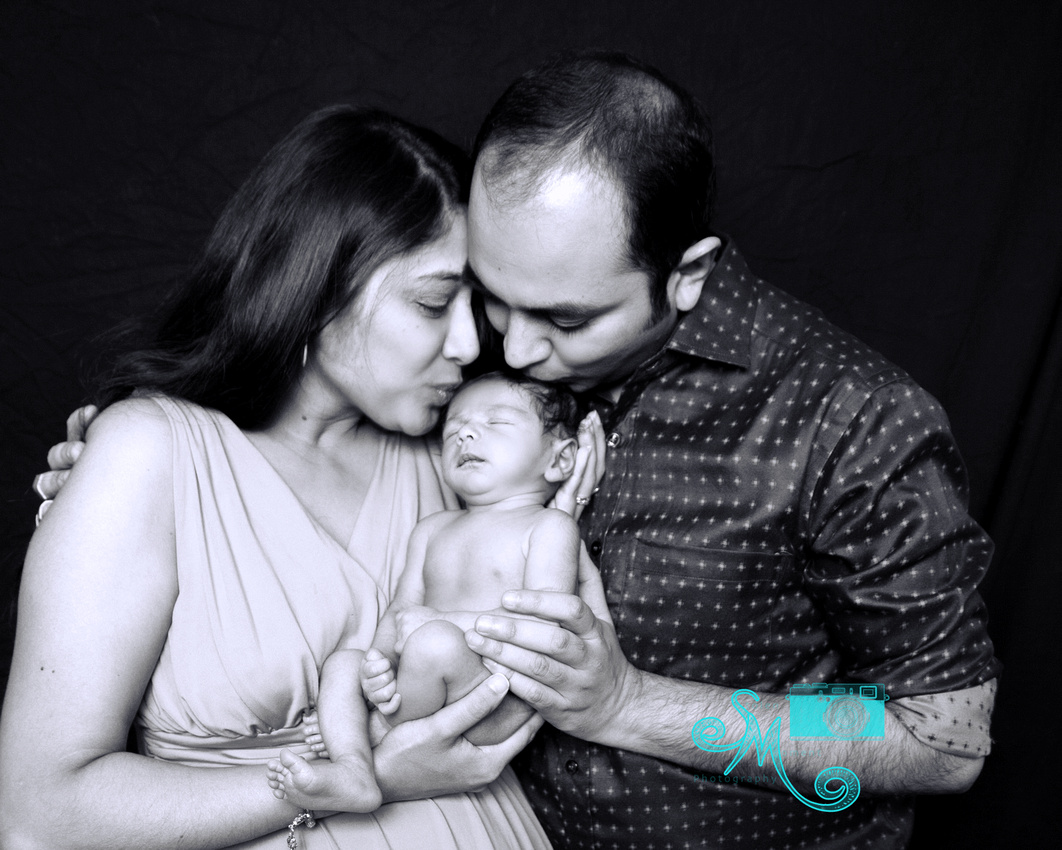 a mom and dad kiss their newborn son on his head