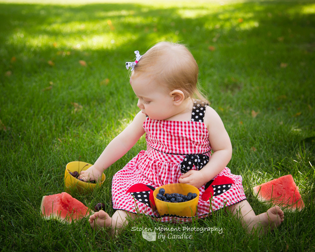 one year old girl sitting amongst a bunch of fruit