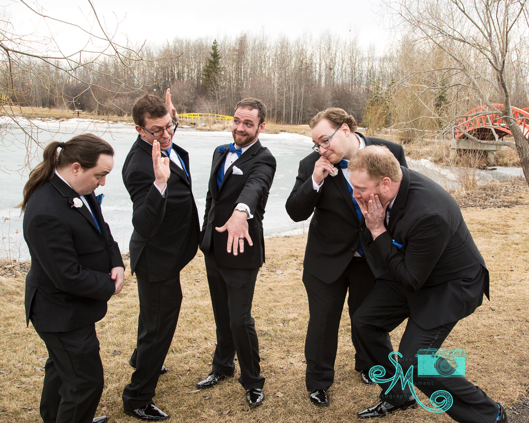 the groom shows off his ring to his groomsmen