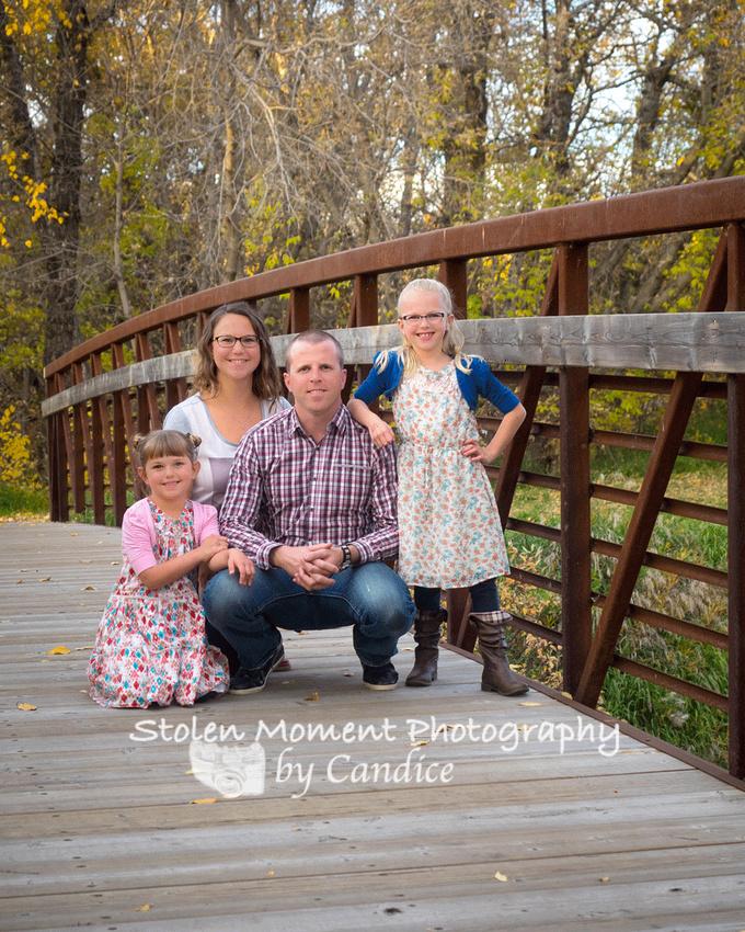 Family of four posing on rustic bridge