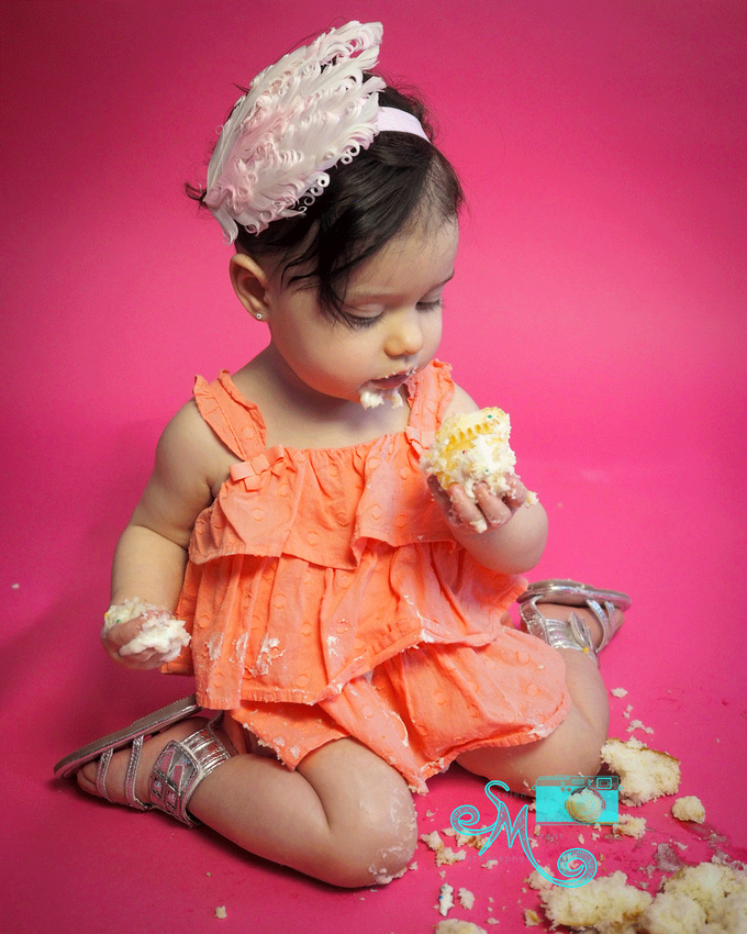 Little girl looking at piece of cake in her hand