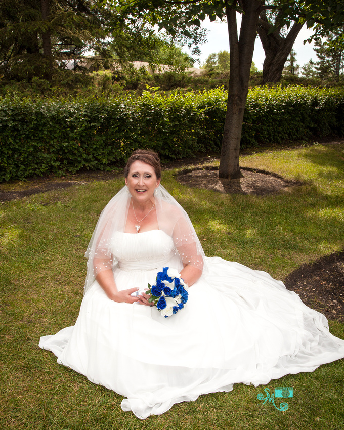bride sitting in grass holding her flowers