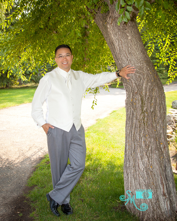 the groom stands next to a tree
