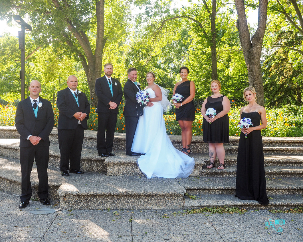 A wedding party stands in front of a forest of green