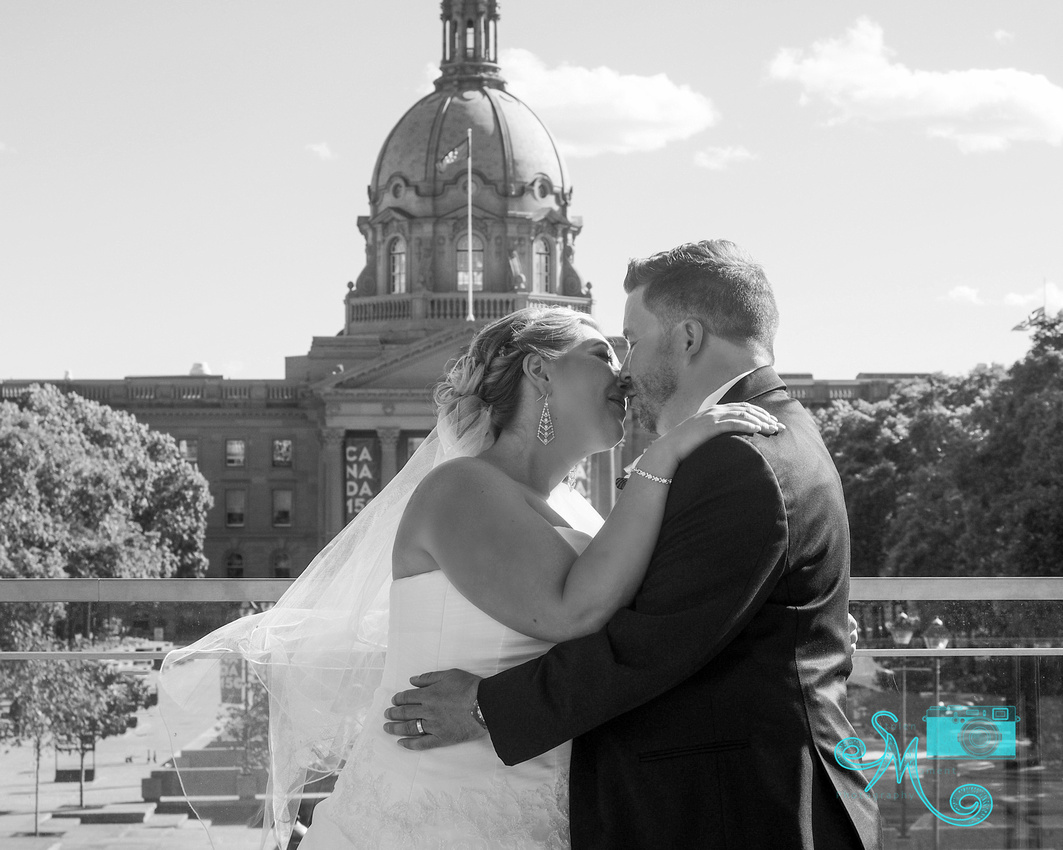 A bride and a groom share a kiss with the Alberta Legislative building in the background