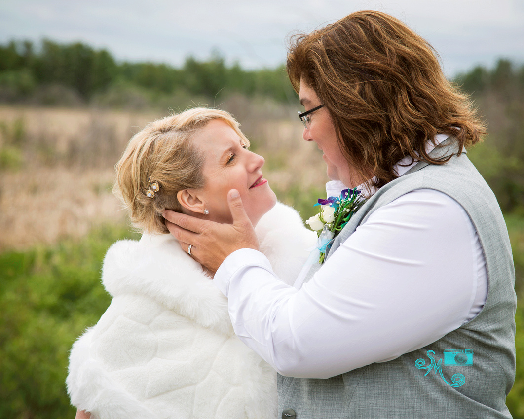 A bride caresses her bride's cheek