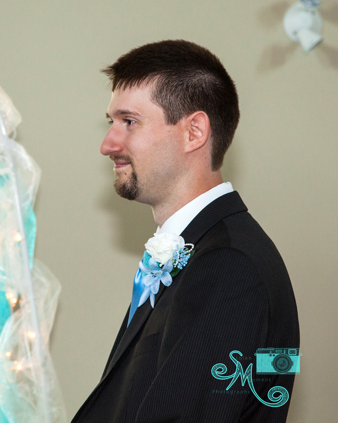 a groom gazes at his bride at the alter