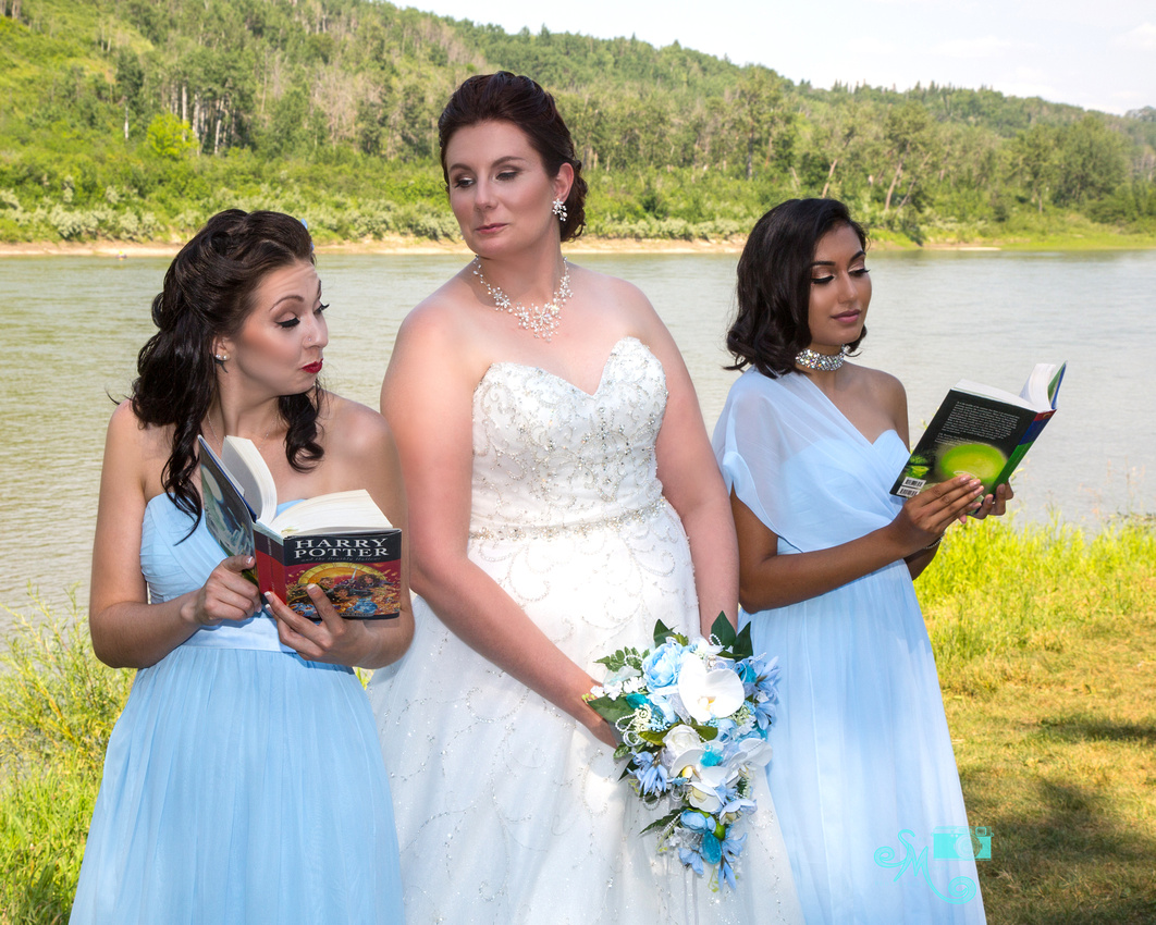 "a bride looks over the shoulder of one of her bridesmaids as she ""reads"" Harry Potter"