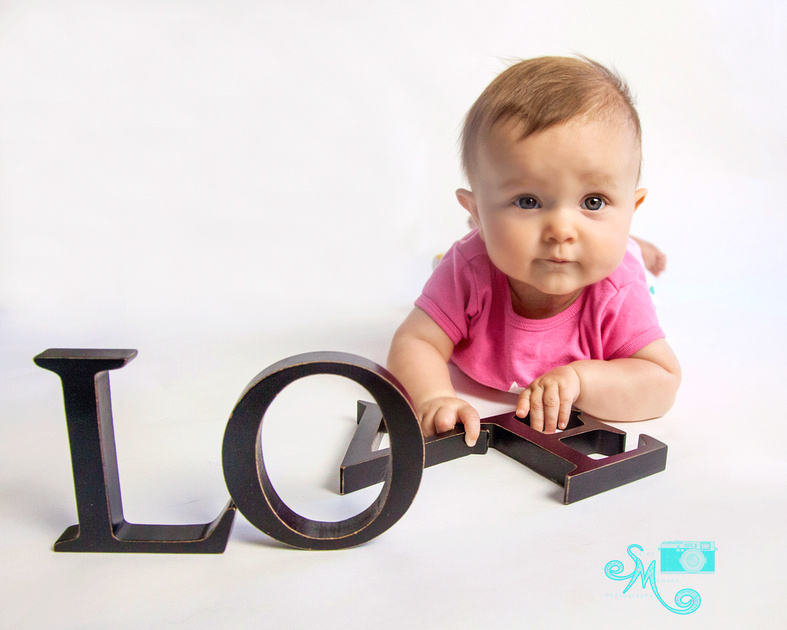 little girl lays on floor with letters LOVE