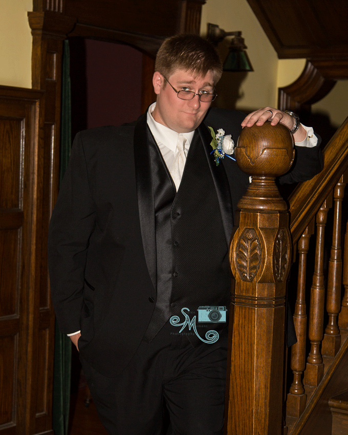 Groom standing by stairs of Rutherford