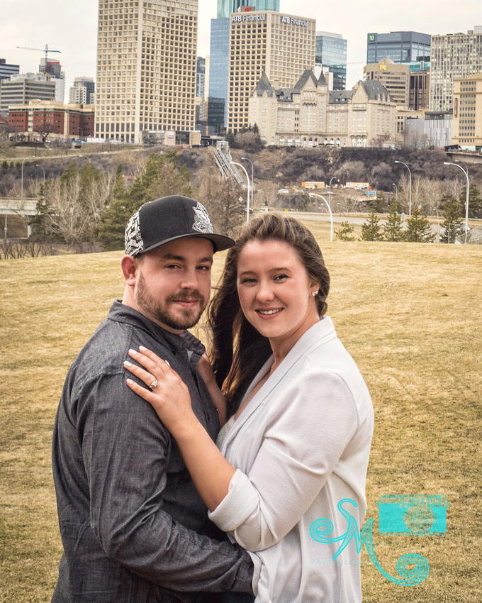 Woman and her fiancé cuddle with Edmonton downtown view in background