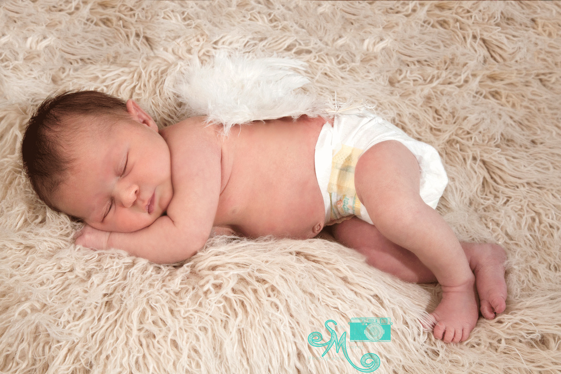 a newborn baby girl sleeping with angel wings on her back