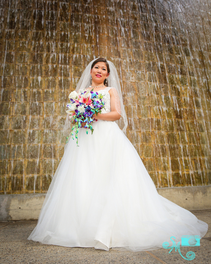 a bride stands in front of Lee Pavilion waterfall
