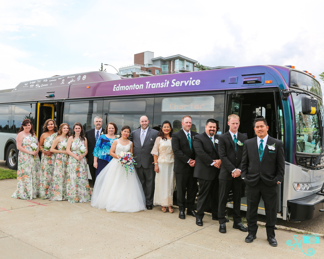 The wedding party and parents stand in front of the ETS platinum bus