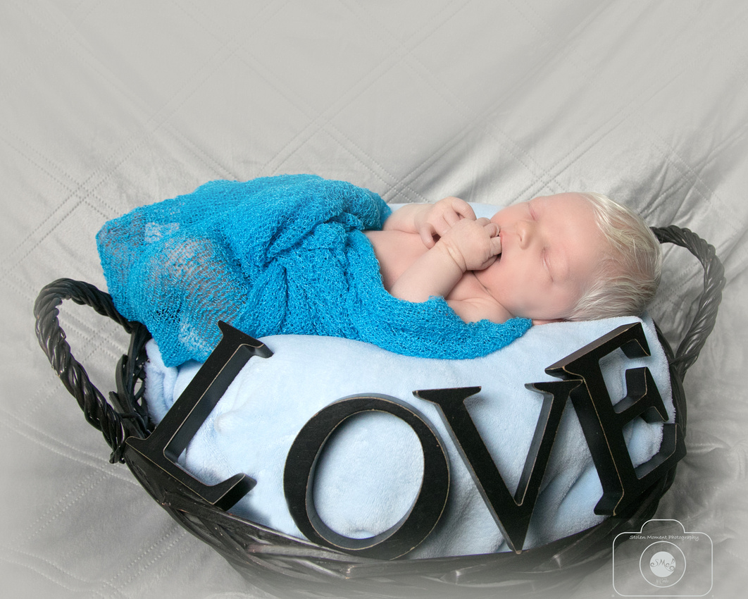 a newborn baby boy sleeps in a basket with the words love in big letters in front of him