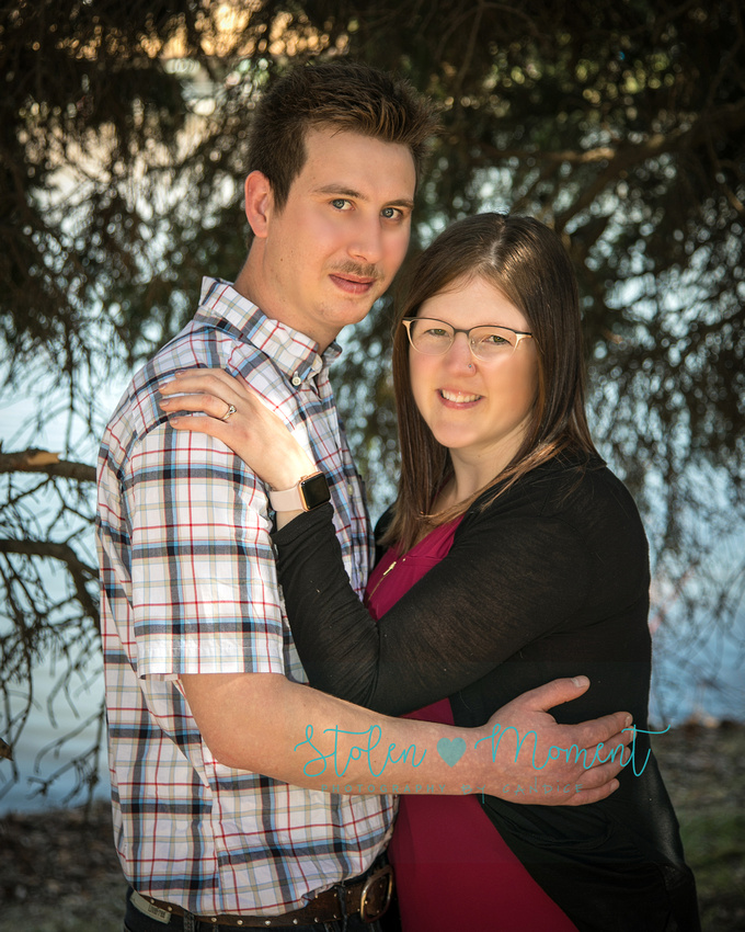 an engaged couple stand in front of the lake at Hawrelak park and smile into the camera