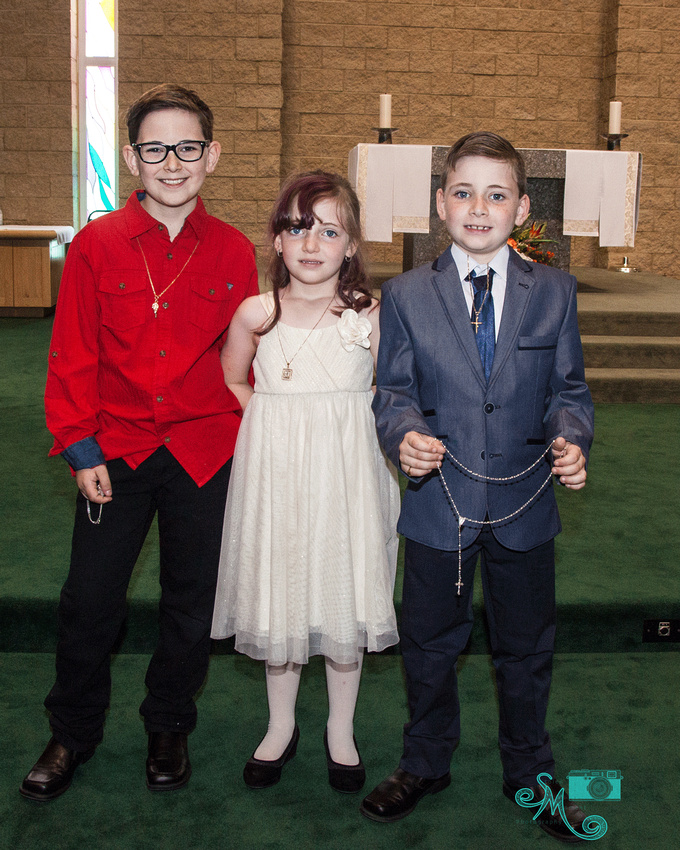 a boy poses with his brother and sister after his first communion