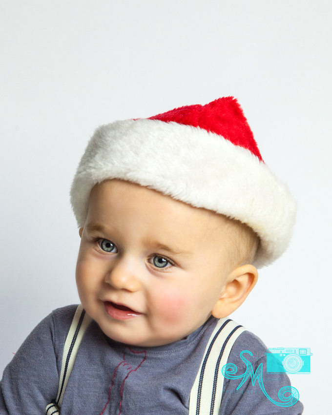 a little boy in Santa hat smiles