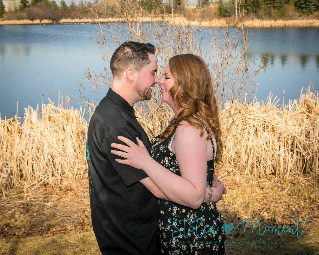 "A man and his fiance stand in front of a lake and ""eskimo kiss"""