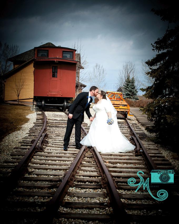 bride and groom on railway tracks kissing