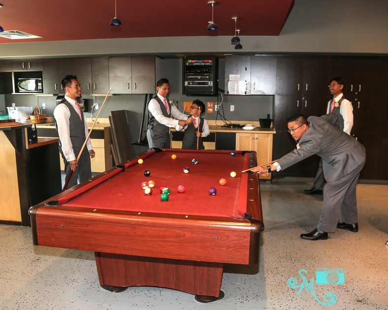 the groom takes a shot at the pool table