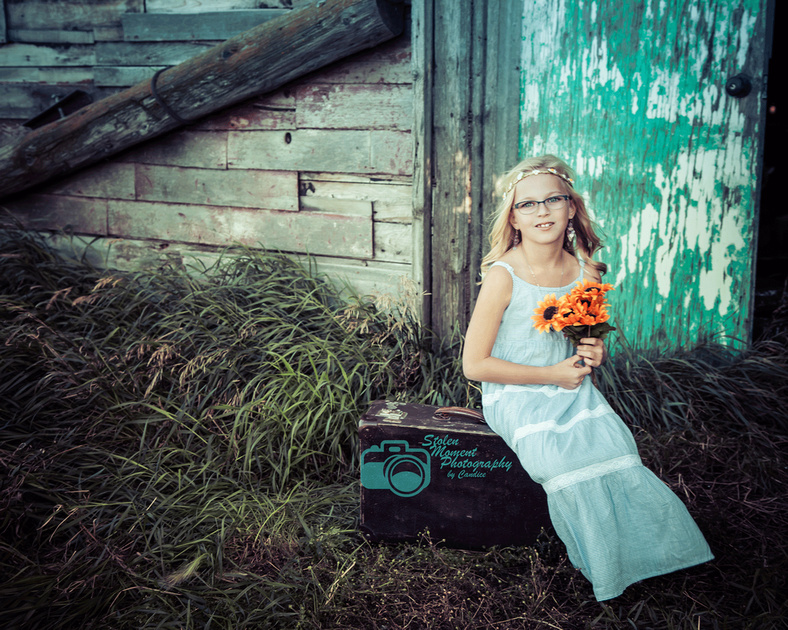 girl sits on suitcase outside barn