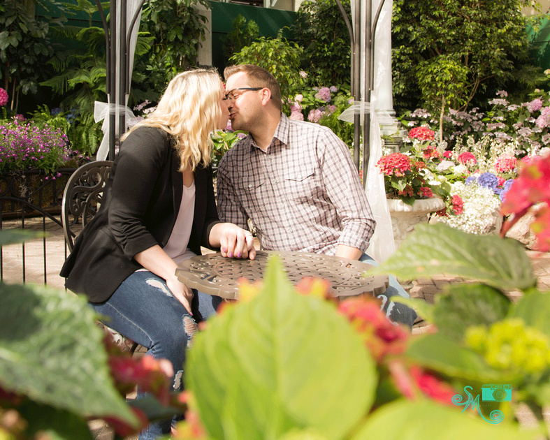 a man and his finance hold hands and share a kiss while sitting at a table in a  gazebo