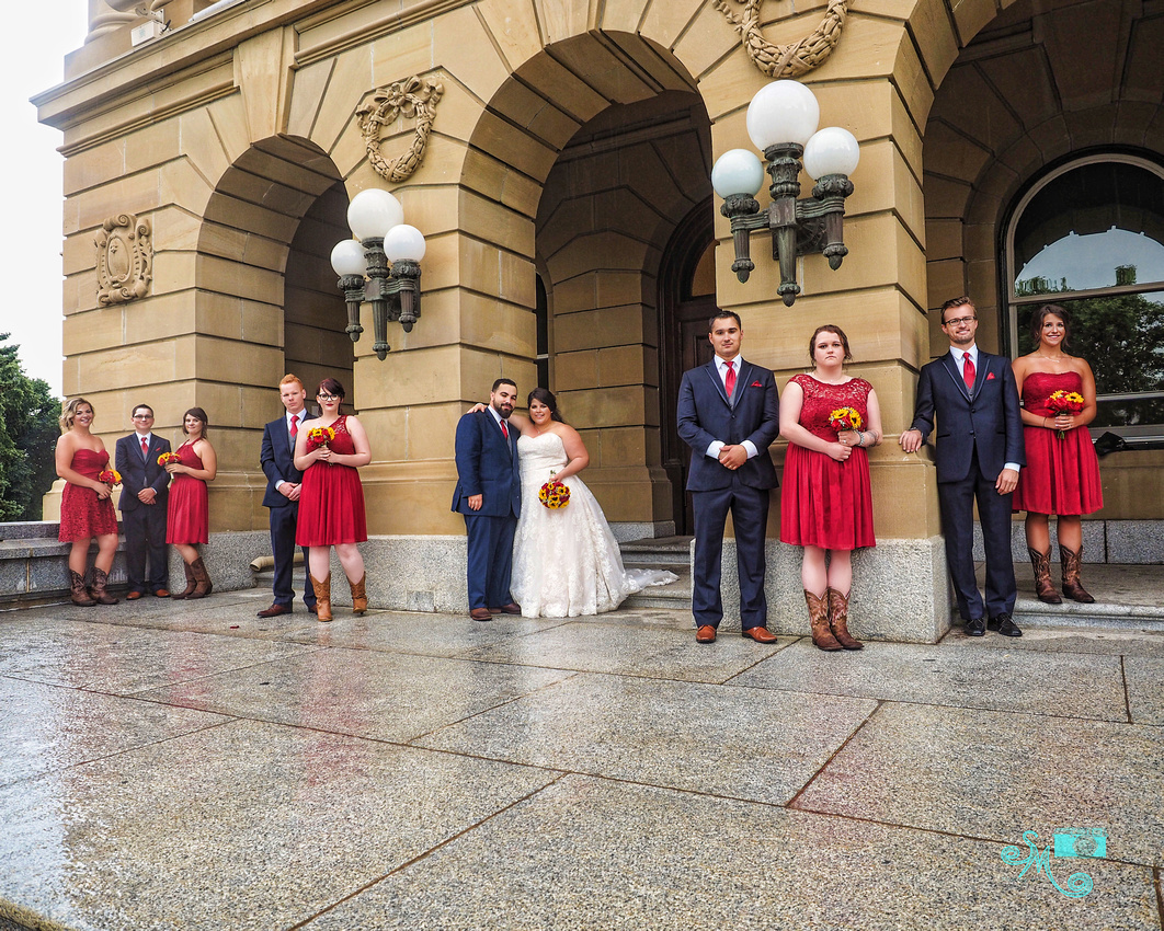 The bride and groom and wedding party stand at the side entrance of the Alberta Legislative building despite the rain