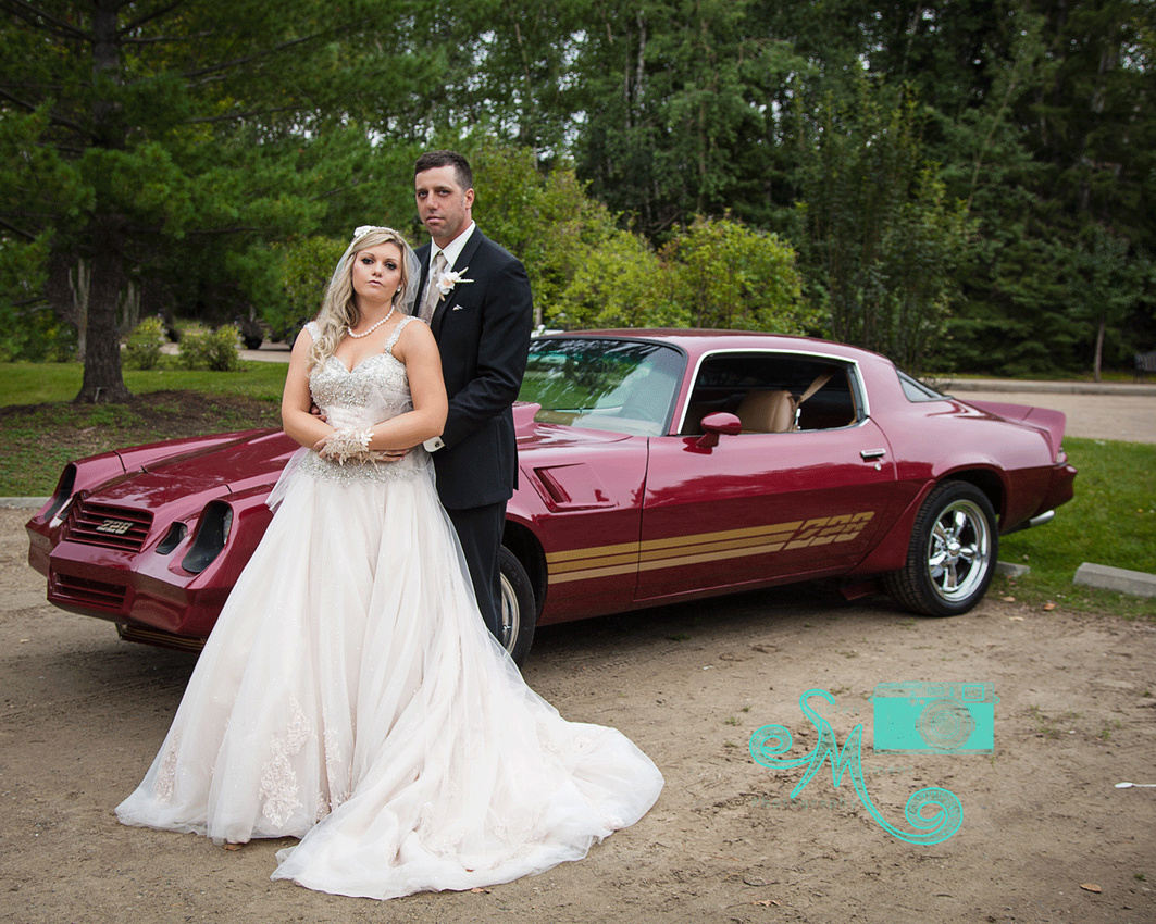Bride and groom pose in front of a 228 Camero