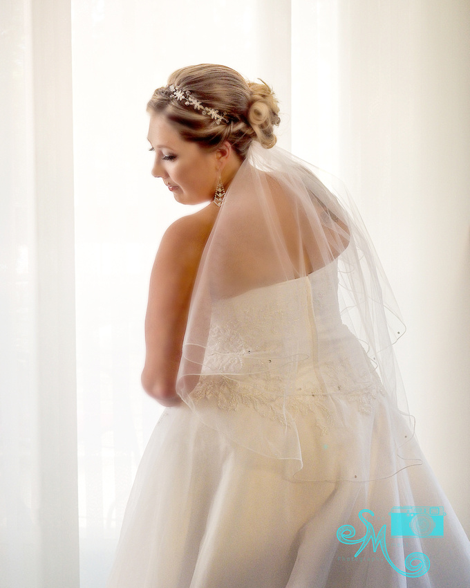 a bride poses in front of a white beautifully lit curtain.