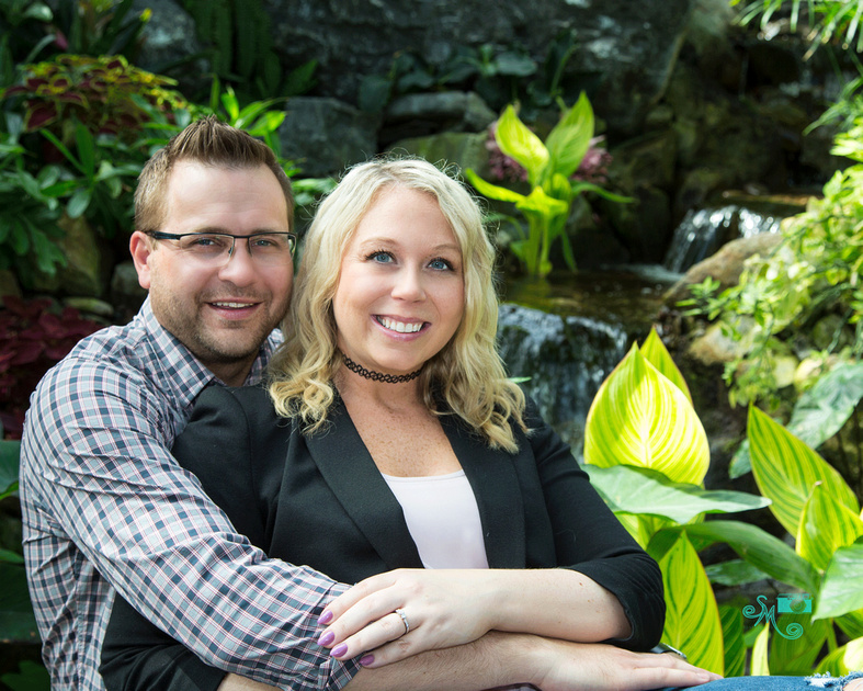 a man cuddles his fiance in front of a waterfall at the muttart conservatory