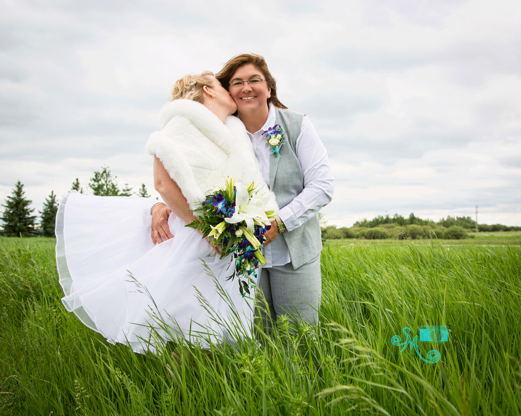 a bride's dress blows up in the wind as she kisses her bride's cheek