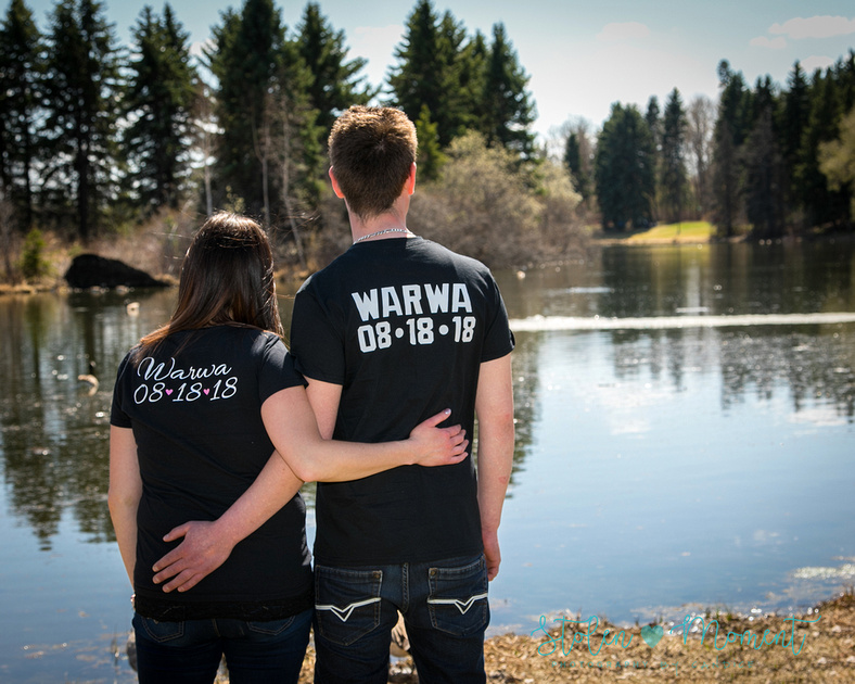 a couple look towards the lake dressed in matching wedding date t-shirts with backs to camera