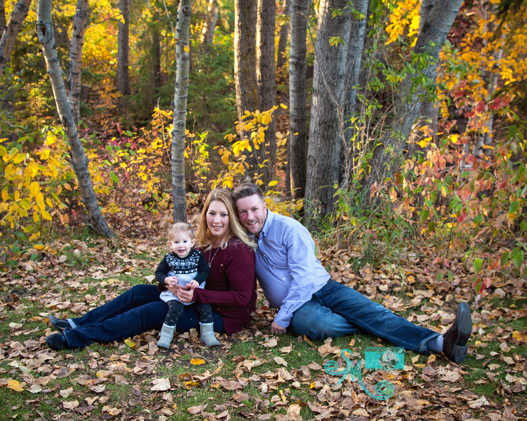 Mom, dad and little girl sit on ground in front of fall coloured bushes in Hawrelak park