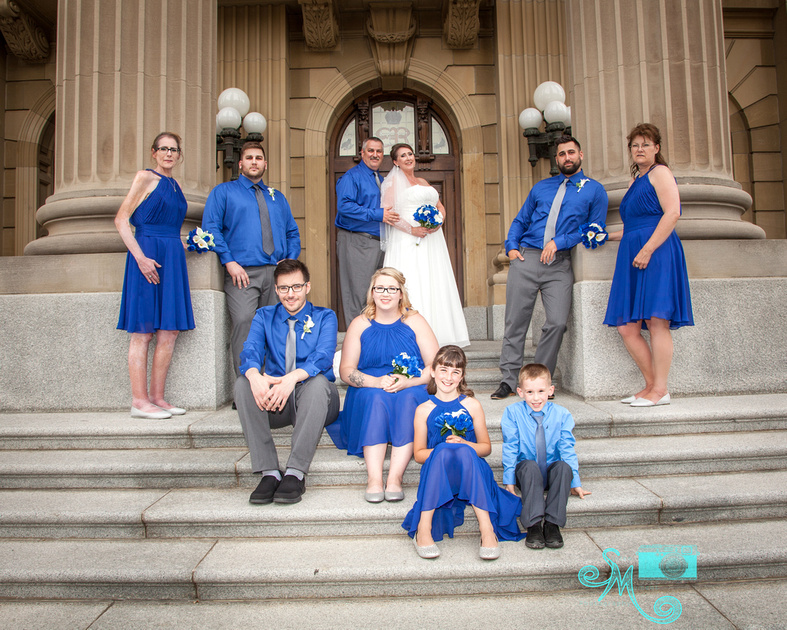 wedding party poses on steps of the Alberta Legislative building