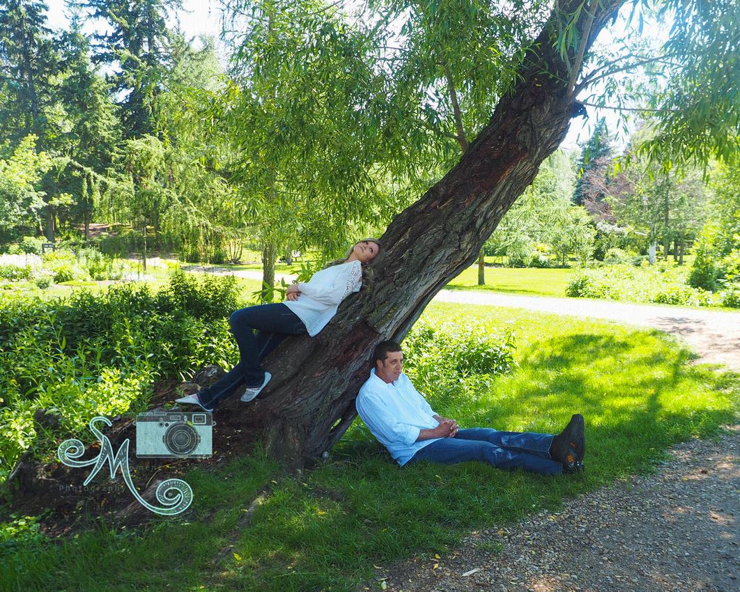 woman laying along tree while man sits at base of tree