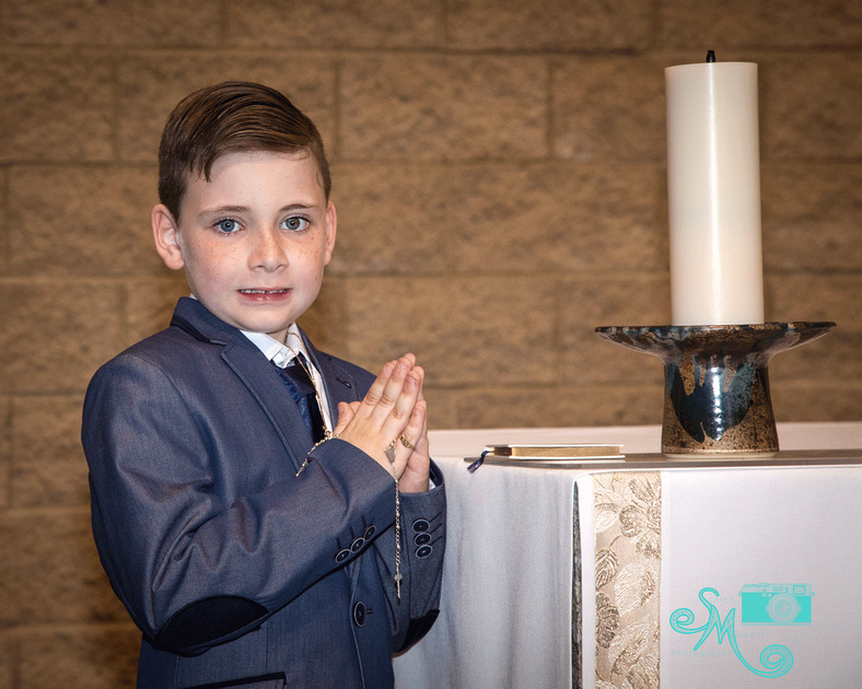 a boy poses at the alter with his rosary