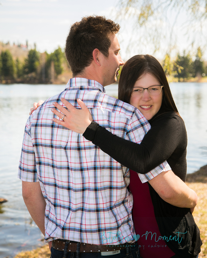 A woman is held in her fiancé's arms while she smiles into the camera while they stand in front of lake at Hawrelak Park